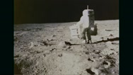 Apollo 11 astronaut carrying rock and soil samples on moon's surface Stock Footage