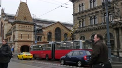 Street traffic scene with red bus in front of the Central Market Hall Stock Footage