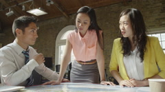 Stock Video Footage of 4K Asian business team in strategy meeting, looking at a map of the world