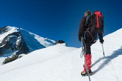mountaineer walking on the glacier during the climb of mont blan - stock photo