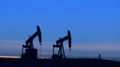 Two pumpjacks pumping crude oil at dusk - stock footage