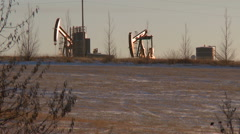 Two pumpjacks pumping crude oil - stock footage