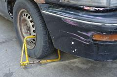 Old vehicle is immobilised by yellow wheel clamp, on road. Stock Photos