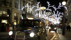 London black cab pulls away on Regent Street Christmas decorations Stock Footage