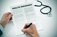 Young man signing a health insurance policy Stock Photos