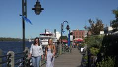 Two women walk along the river walk, wilmington, nc, usa Stock Footage