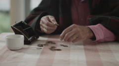 4K Confused senior man trying to count out coins from a purse - stock footage
