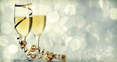 champagne glasses against holiday lights - stock photo