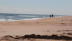 Man & Women walking on vacant beach Stock Footage
