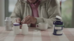 4K Portrait of senior man taking pills from several containers of medication - stock footage