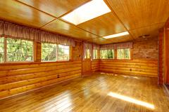 Bright empty log cabin house interior with skylights Stock Photos