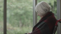 4K Portrait of lonely senior lady sitting by the window looking over to her meds Stock Footage