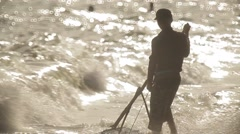 Fisherman with heavy fishing tackle collects seashells on the beach. Sea surf. Stock Footage