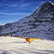 Yellow airplane landing to  alpine resort in swiss alps in winter Stock Photos