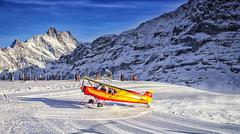 Yellow airplane landing to  alpine resort in swiss alps in winter2 Stock Photos