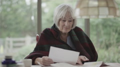 4K Portrait of senior woman worrying about paying the bills - stock footage