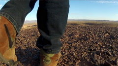 Feet And Legs Of Man Walking In Barren Rocky Desert Stock Footage