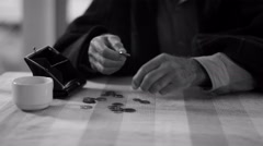 4K b&w Confused senior man trying to count out coins from a purse - stock footage