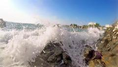 Super wide angle view of foamy splashing ocean tide waves washing over rocky Stock Footage