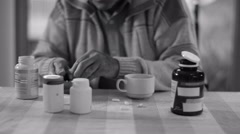 4K b&w Portrait of senior man taking pills from several containers of medication - stock footage