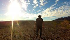 Man Walks Away From Camera In Rocky Desert Under Blazing Sun Stock Footage