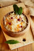Sauerkraut - Sour cabbage -  on wooden bowl with bay leaves Stock Photos