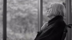 4K Black & white portrait of  senior woman sitting by window with meds on table Stock Footage