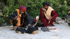 Stock Video Footage of Two snake charmer enchanting cobras in a street of Manali, India.
