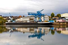dockyard on river main in germany with reflection in the river - stock photo