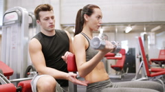 Young couple with dumbbell flexing muscles in gym Stock Footage