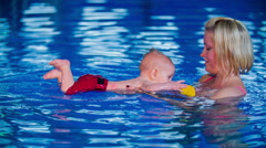Newborn splashing in the swimming pool Stock Footage