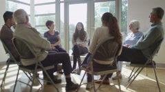 4K People in group therapy session talk about their problems in sunlit room - stock footage