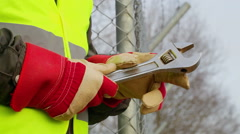 Worker with  adjustable wrench at outdoors near fence Stock Footage