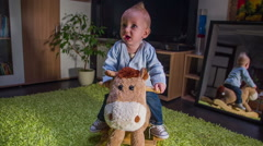 Weary young child riding plush hoers Stock Footage