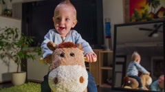 Weary small child is smiling while riding a plush horse - stock footage