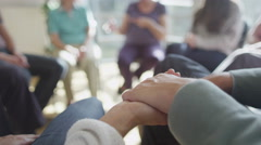 4K Couple holding hands for support during group therapy session. Focus on hands Stock Footage