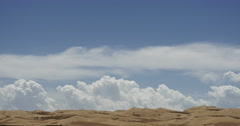 4k timelapse large white puffy cloud mass rolling over desert sand dunes. Stock Footage