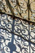 Wrought iron door to the garden with beautiful shadow Stock Photos