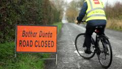 Cyclist turning around at Road Closed sign Stock Footage
