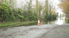 Traffic cone at flooded road, warning sign for inundated street Stock Footage