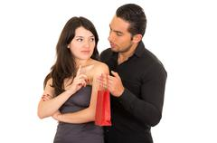 Young beautiful woman refusing to accept gift from man Stock Photos