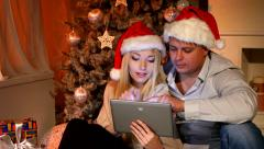 Couple near christmas tree in christmas decorated house with tablet pc Stock Footage
