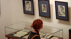 The schoolgirl examines portraits and other subjects presented at an exhibition Stock Footage
