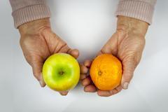 rheumatoid arthritis hands and fruits - stock photo