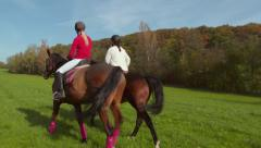 2 Girls Riding Meadow Stock Footage
