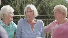 4K Happy female senior friends chatting and laughing together outdoors - stock footage
