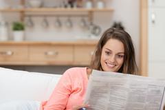 Attractive woman enjoying the morning newspaper Stock Photos