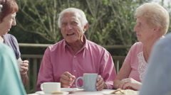 4K Group of senior friends chatting together in the garden with cups of tea Stock Footage