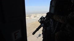 Machine gunner during a tactical flight over the mountains of Afghanistan Stock Footage