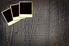 Old weathered blank instant photos on dark wooden table Stock Photos